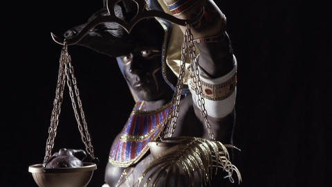 Egyptian god Anubis is holding the golden scale with a heart and fern leaf Live Action