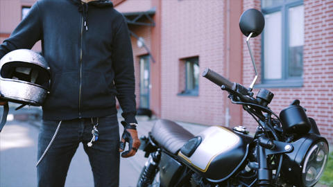 Biker goes to his cool and custom motorcycle in a big city Live Action