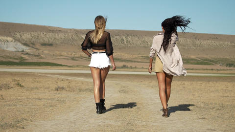 Two slender sexy women are walking along a country road. They are wearing shorts Live Action