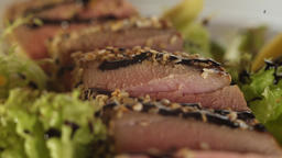 Balsamic sauce droplets fall on tuna pieces and green salad leaves on a plate Live Action