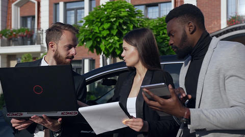 Good-looking business people discussing the nuances of a car purchase agreement Live Action