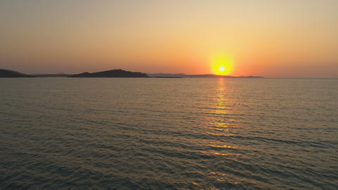 Orange and golden sunset over sea horizon in Greek island Live Action