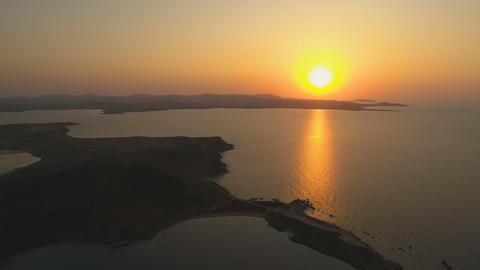 Majestic sunset with huge orange sun over island shore line Footage