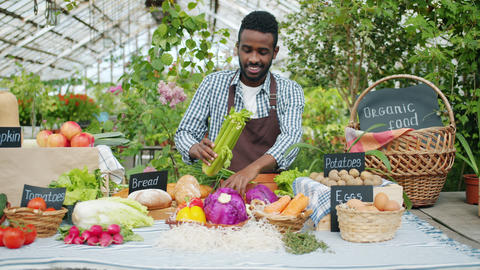 African American salesman putting fresh organic vegetables on table at farm sale Footage