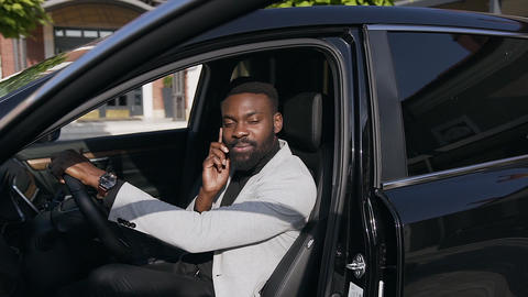 Elegant bearded african american man in white jacket sitting at the driver's Footage
