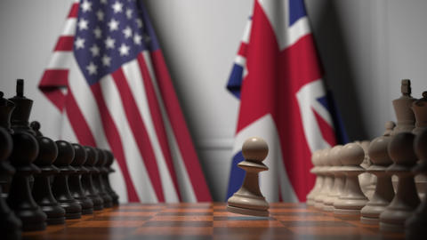 Flags of United States and United Kingdom behind chess board. The first pawn Live Action