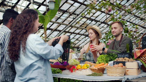 Young farmers selling organic vegetables to consumers in greenhouse market Live Action