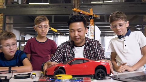 Young Korean man of electronics engineer with young children using screwdriver Live Action