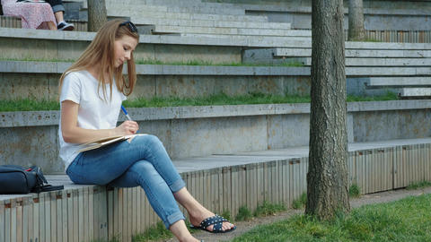 Young beautiful girl in a park writes to a notebook. A student writes poetry Live Action