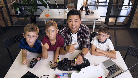 Top view of portrait shot of male handsome teacher and kids posing to the camera Live Action
