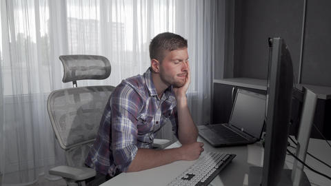 Handsome man falling asleep in front of his computer Live Action