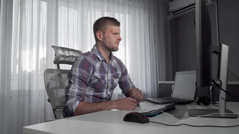 Upset male freelancer sitting in front of his computers Live Action