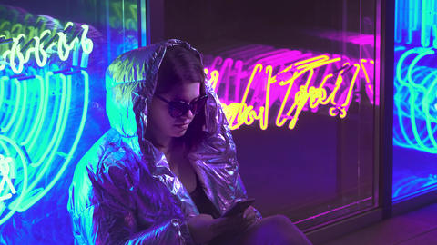 Young girl messaging in cellphone chat app. Dark place with mixed coloured light Live Action