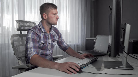 Handsome IT office worker using two computers working on a project Footage