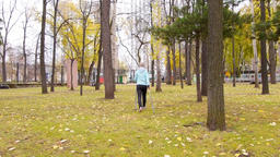 Woman practicing Nordic Walking in an autumn park, she's walking away from the Live Action