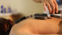young woman in spa salon with hot stones in spa salon.Close-up Live Action