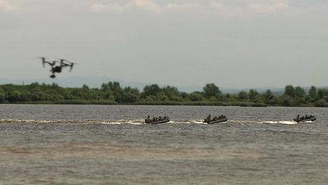 Marines, with weapons in their hands, move on military boats on the river, military action on the Live Action