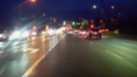 Driving City Street at Night With Blur Effect. Driver Point of View POV of Urban Traffic While Footage