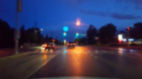 Driving City Street at Night While Raining With Blur Effect. Driver Point of View POV of Urban Footage