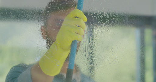 Man removing cleaning solution from glass with special tool, cleaning service Live Action