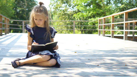Adorable little school girl with notes and pencils outdoor. Back to school Footage