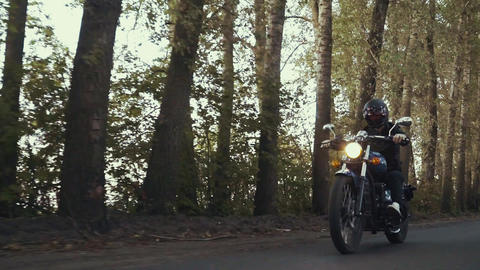 A guy in a black leather jacket and helmet riding a classic motorcycle on a Live Action