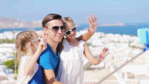 Family vacation in Europe. Father and kids taking selfie background Mykonos town Live Action