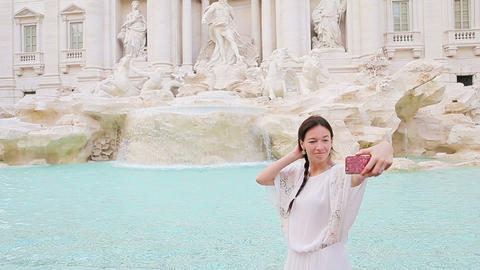 Young woman with smart phone taking selfie outdoors in european city near famous Footage