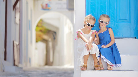 Cute little girls at street of typical greek traditional village with white Footage