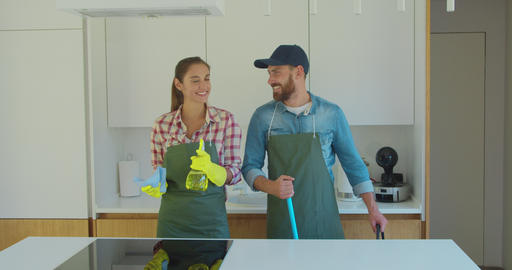 Man and woman as a professional cleaners in uniiform having fun during the work Footage