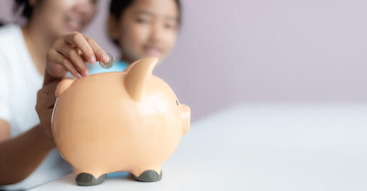 Mother and daughter putting coin into the piggy bank 004 フォト