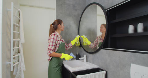 Young woman as a professional cleaner in uniform cleaning bathroom. Cleaning Live Action