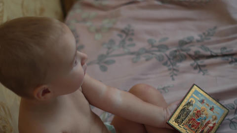 A small child kisses the icon of God in his hands. The action in Slow motion Live Action