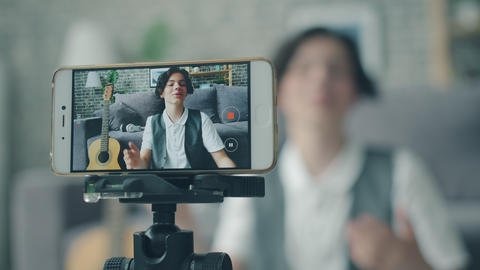 Portrait of happy teen recording video vlog with smartphone talking gesturing Live Action