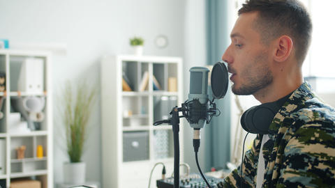 Attractive guy speaking in microphone recording podcast for online blog Live Action