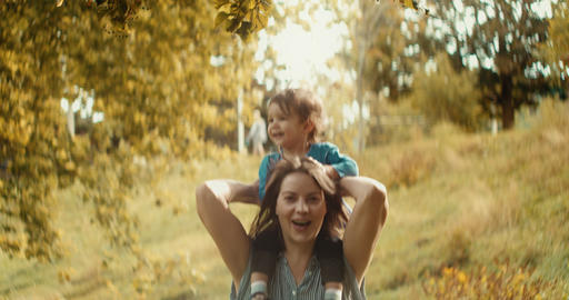 Mother and baby girl playing outside during the early fall season Footage