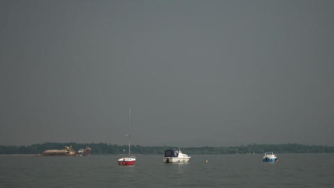 A small yacht sways on the surface of the water in cloudy weather Live Action