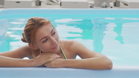 Gorgeous woman relaxing in outdoors swimming pool Live Action