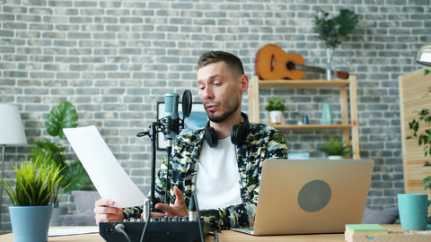 Good-looking guy reading information in microphone making podcast in studio Live Action
