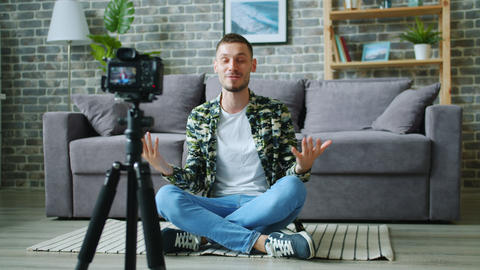 Man vlogger recording video for blog talking gesturing using camera on tripod Live Action
