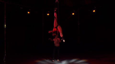 Two acrobats rotating under circus dome keeping vertical position at night Footage