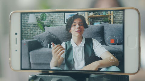 Portrait of happy teenager recording video for vlog with smartphone camera Live Action