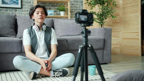 Creative boy vlogger recording video for online vlog speaking on floor at home Live Action