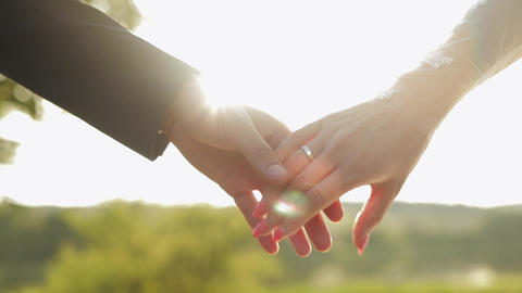 Hands of bride and groom in sunbeams. Wedding couple. Happy family. Newlyweds Live Action
