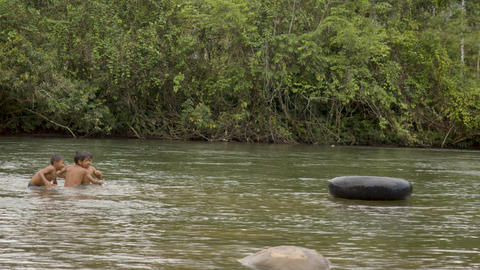 Indigenous Boys Are Playing In A River With A Floating Tire In Ecuador Live Action