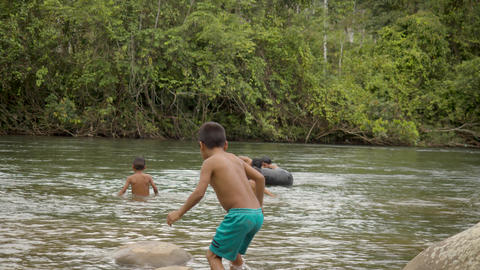 Indigenous Boys Plays With Floating Tire And Swim In Their Local River In Ecuador Live Action