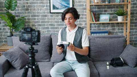 Teenage blogger recording video about modern headphones speaking about device Footage