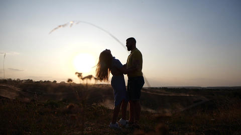 Silhouette of a charming young couple in rural landscape at sunset. A couple in Footage