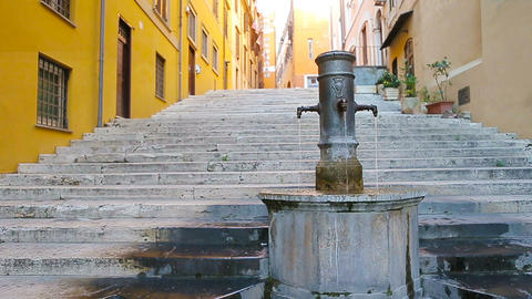 Street fountain in a European city on the street. People quench thirst drinking Live Action