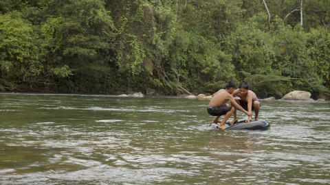 Two Indigenous Boys Are Playing In A Water With A Floating Tire In Ecuador Live Action